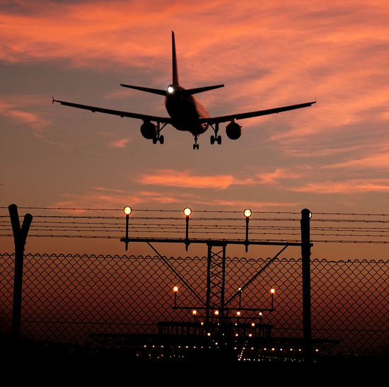 Low Angle View Of Airplane Flying Above Fence During Sunset