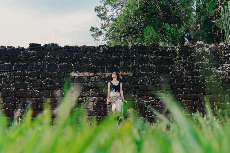 Full Length Of Woman Sitting Against Stone Wall