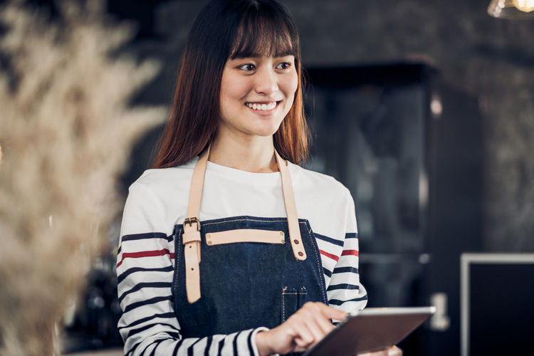 Smiling barista using digital tablet in cafe