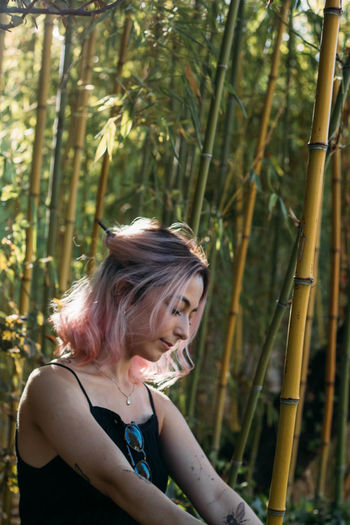 Close-up of young woman with closed eyes sitting in forest