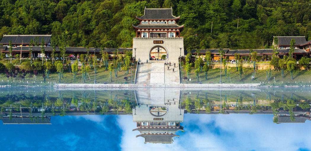 View of building with reflection of trees in lake