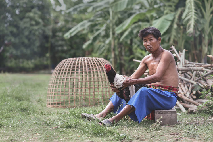 Portrait of shirtless man holding rooster while sitting against trees