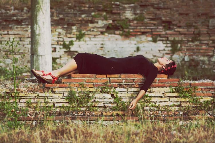 Side view of woman lying on retaining wall at park