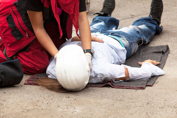 Paramedic performing cpr on person women on street