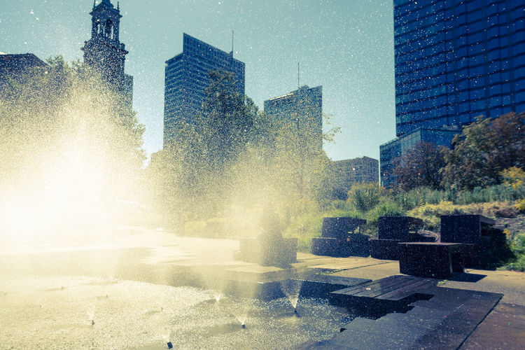 Fountain by buildings in city against sky