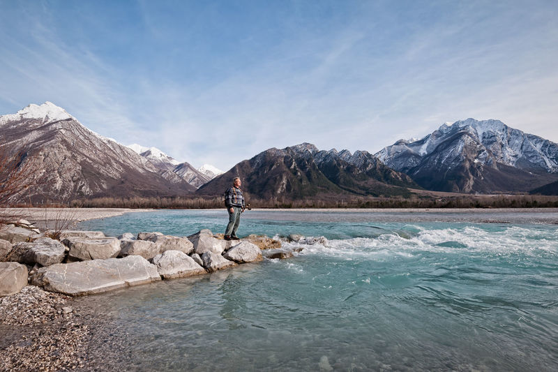 Man Standing On Rocks By Lake Against Mountains