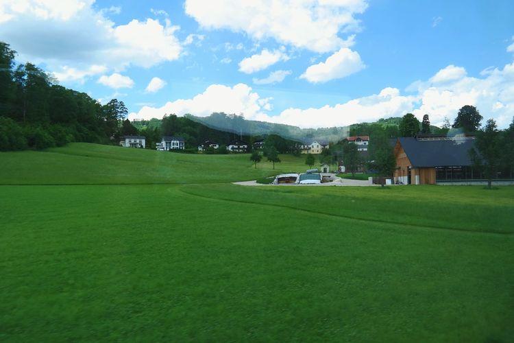Houses on grassy landscape against the sky