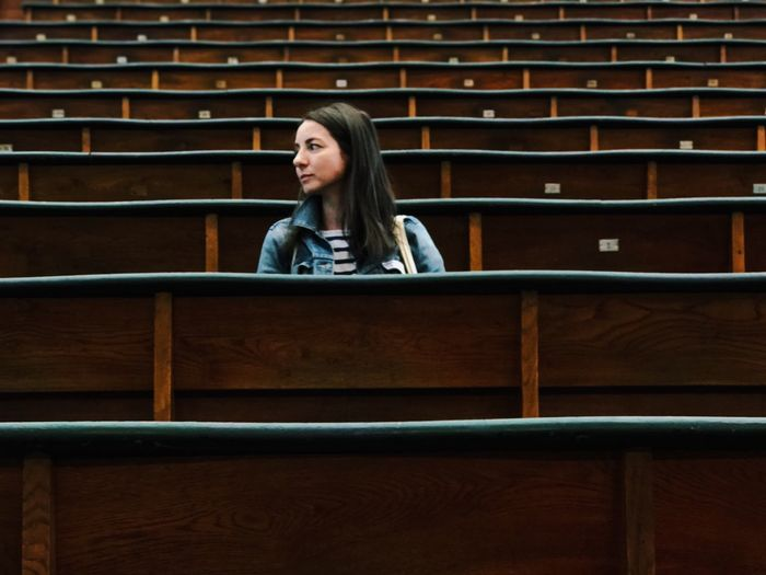 Young woman sitting amidst benches in lecture hall at university