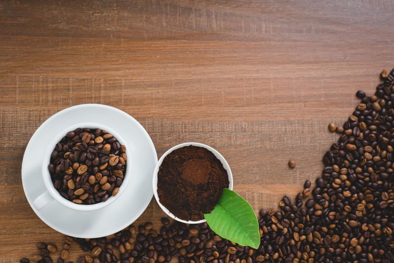 Coffee cup and coffee beans , flat lay image with copy space for your text Table Food And Drink Food Freshness Roasted Coffee Bean Coffee - Drink Still Life Indoors  Coffee Brown No People High Angle View Wood - Material Cup Healthy Eating Directly Above Drink Wellbeing Large Group Of Objects Refreshment Caffeine