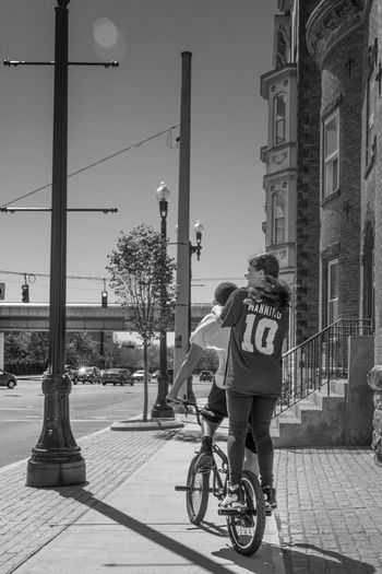 Rear view of man riding bicycle on city street