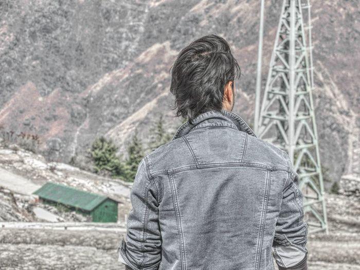 Rear view of man wearing jacket looking at mountain