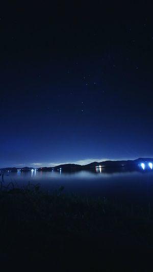 View of illuminated riverbank at night