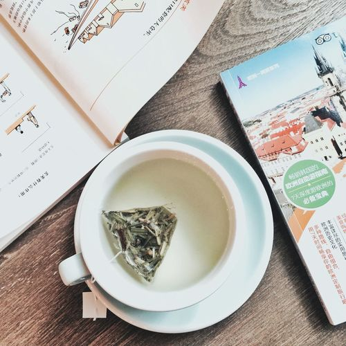 High Angle View Of Green Tea With Books On Table