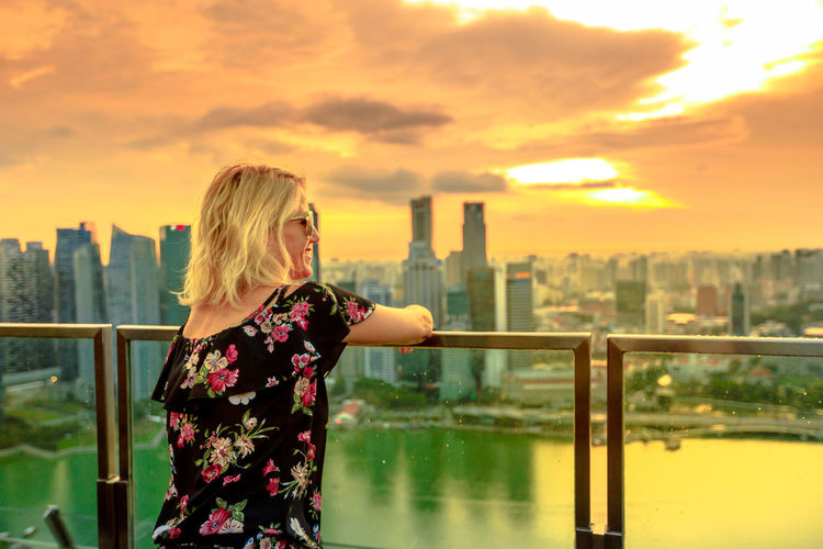 Carefree tourist at observation deck over financial district skyscrapers. Happy girl looking panorama from rooftop in South Marina, Singapore. Aerial view of cityscape skyline at sunset. Singapore Singapore City Woman Tourist Tourist Attraction  Tourist Destination People Girl Females Aerial View Skyline Cityscape Panorama Happy Travel Hat Lifestyle Enjoy Nature Tourism Architecture Sky One Person Built Structure Building Exterior City Sunset Standing Water Real People Women Leisure Activity Lifestyles Waist Up Hair Building Blond Hair Outdoors Office Building Exterior Hairstyle Skyscraper