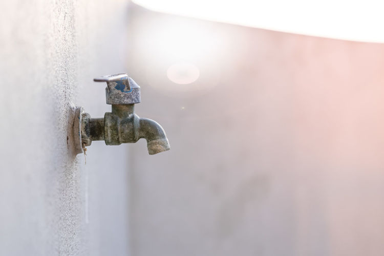 Close-up of old faucet against wall