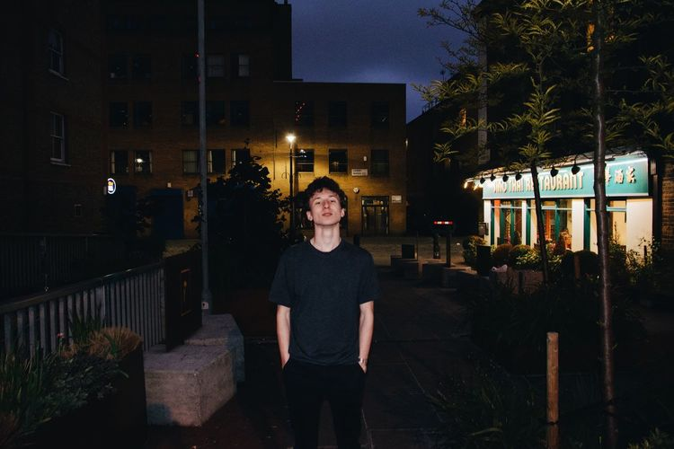 Portrait of young man standing against illuminated building at night
