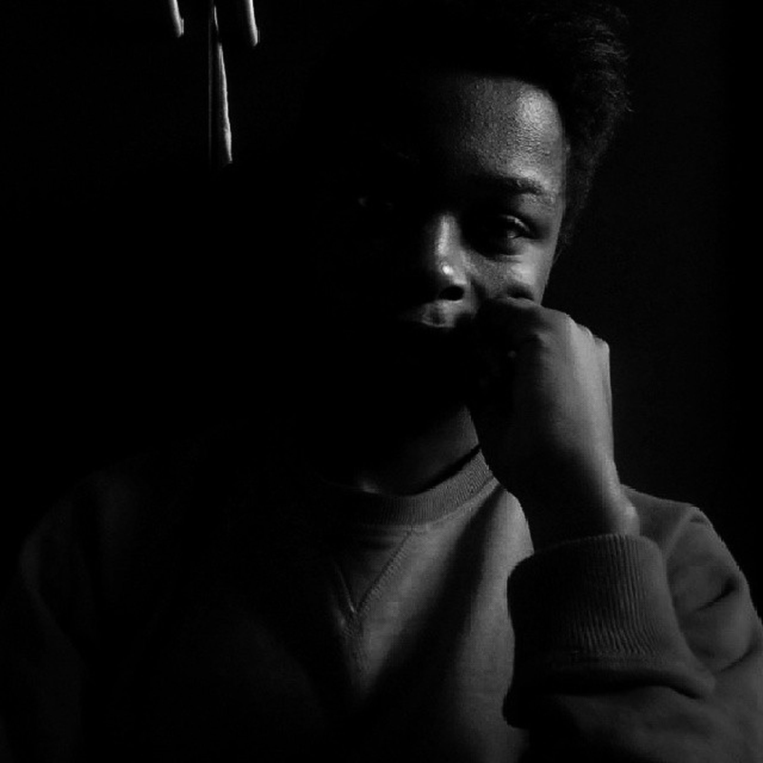 indoors, young adult, person, headshot, lifestyles, front view, contemplation, young men, portrait, studio shot, serious, leisure activity, looking at camera, head and shoulders, black background, casual clothing