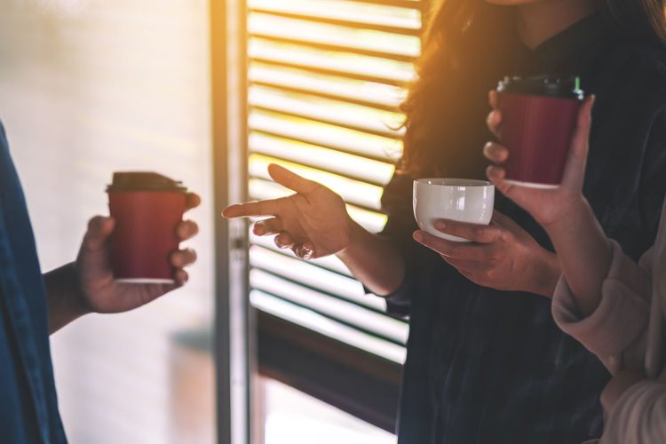 Midsection of people holding disposable coffee cup while discussing in office
