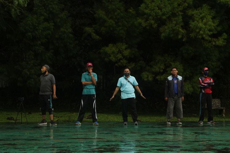 People standing against trees