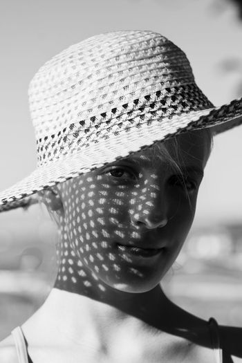 Close-up portrait of a girl wearing hat
