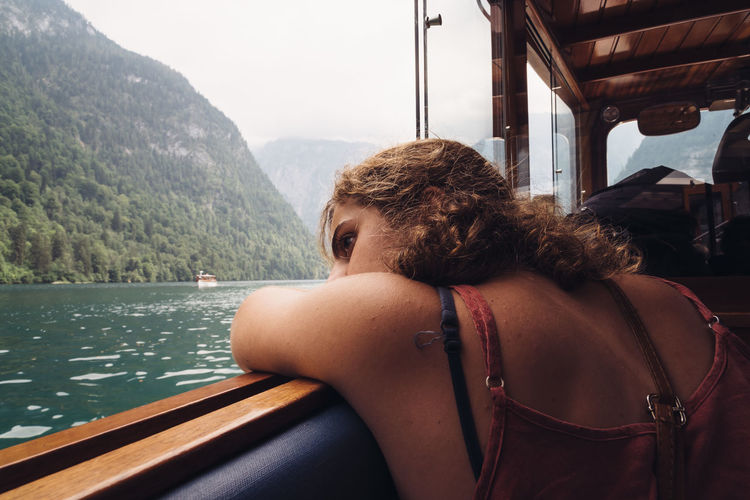 Girl looking at the lake on the ship Königssee Obersee Alps Beauty In Nature Day Headshot Journey Lake Leisure Activity Lifestyles Melancholy Mode Of Transport Mountain Nature Nautical Vessel One Person Outdoors People Real People Rear View Sitting Sky Transportation Vehicle Interior Vehicle Seat Water Window Young Adult Young Women
