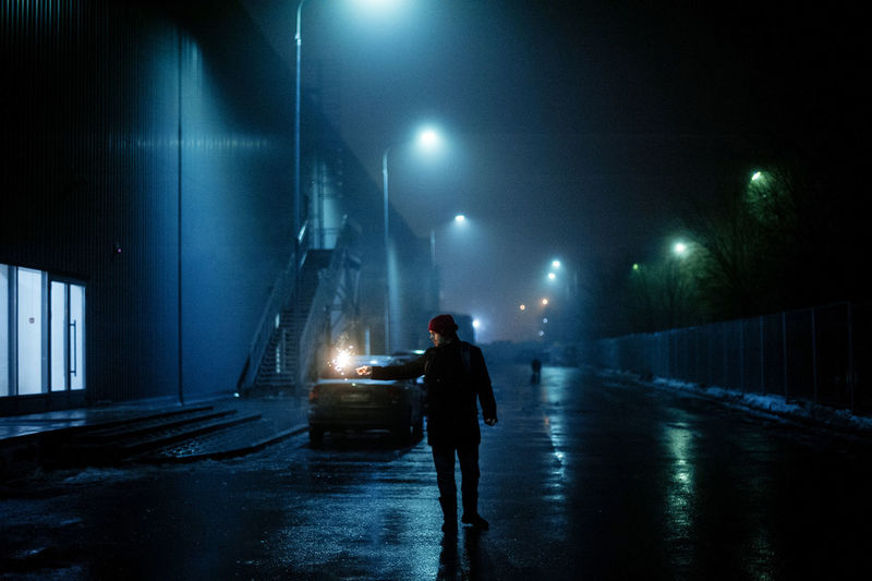 Man standing on illuminated road against sky at night