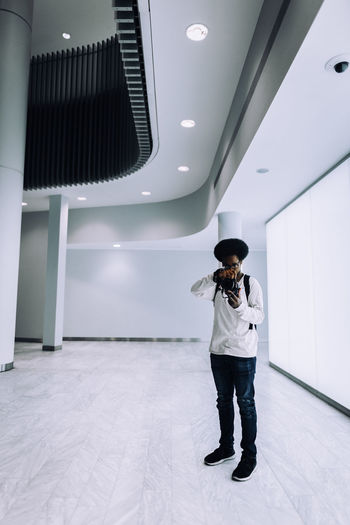 Adult Architecture Casual Clothing Ceiling Flooring Front View Full Length Indoors  Leisure Activity Lifestyles Men Mid Adult Occupation One Person Real People Standing Technology Uniform White Color Young Adult Young Men