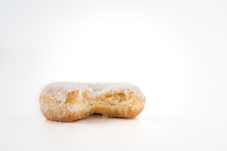 partially eaten donut on white background with copy space   daylight food photography White Background Food And Drink Food Single Object Studio Shot Close-up Copy Space Baked Macro Still Life Sweet Food No People Donut Copy Space Partially Eaten