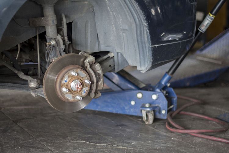 Mechanician changing car wheel in auto repair shop. Industrial Industry Repairs Service Tires Auto Repair Shop Car Close-up Day Dirty Equipment Garage Indoors  Installation Instrument Jack Land Vehicle Mode Of Transport No People Tire Tools Transportation Vehicle Part Wheel Wheels