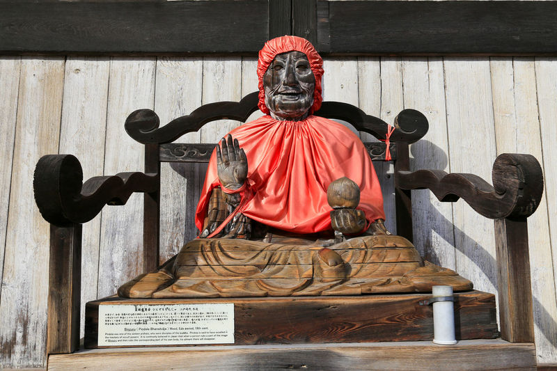 Statue of man sitting on seat against wall