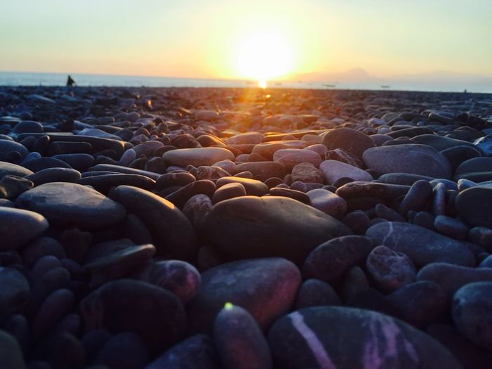Surface level of pebbles at shore against sky during sunset