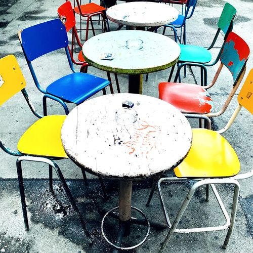 High angle view of empty chairs and tables at sidewalk cafe