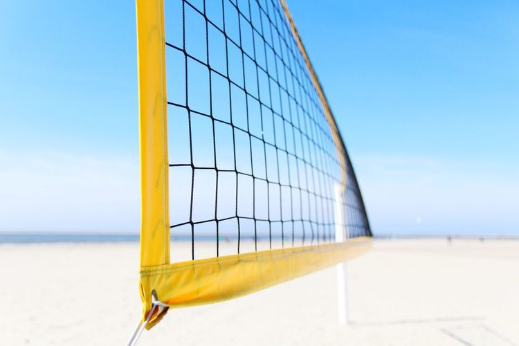 Volleyball net at beach against blue sky