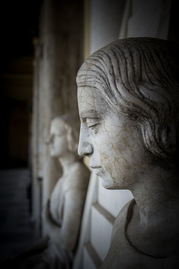 Profile of young sad woman, In the background another statue of a woman and the hall of the museum. Ancient Antique Art Art And Craft Art, Drawing, Creativity Carved Classic Corridor Craftmanship European  Face Female Femininity Handsome Heritage Marble Museum Old Profile Sacred Sad Sadness Statue Stone Women