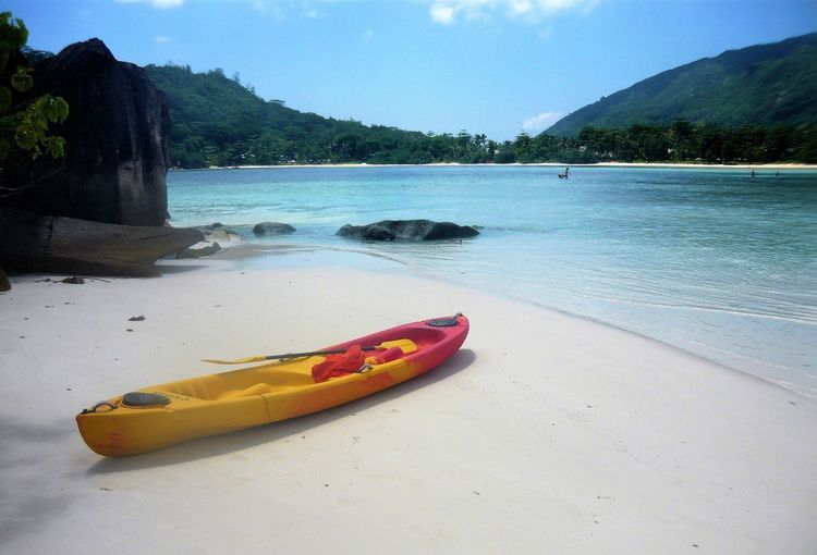 Mahe, Seychellen Mahe, Seychellen Beach Beauty In Nature Canoe Day Floating On Water Inflatable Raft Kayak Moored Mountain Nature Nautical Vessel No People Oar Outdoors Outrigger Pedal Boat Pool Raft Sea Seychellen Sky Tranquility Transportation Water