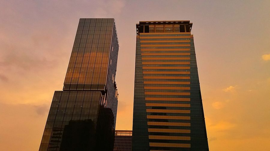 Golden hour. Architecture Skyscraper Low Angle View No People Two Towers Perspectives Urban Scene Sunset Silhouettes Orange Color Urban Landscape EyeEm Manila Eyeem Philippines Mobilephotography Mobilephotographyph Silhouette Malephotographerofthemonth Sky Cityscape Urban Skyline Building Exterior Low Angle View EyeEm Selects Architecture Golden Hour (Samsung J5 2016) Colour Your Horizn