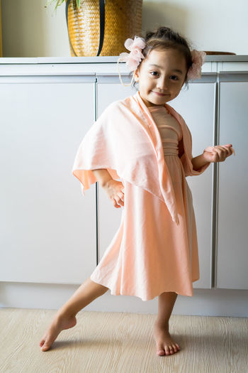 A little girl is standing in a beautiful dress with hair accessories. pretend play at home.
