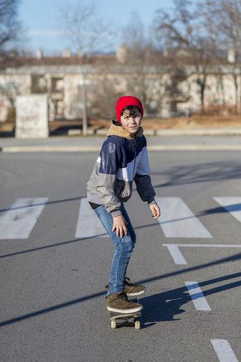 Full length boy skateboarding outdoors