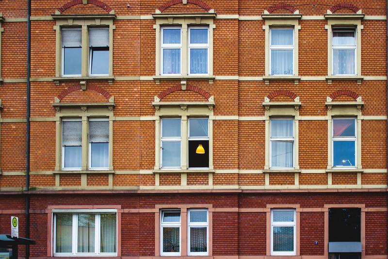 A brick facade with light shining through windows