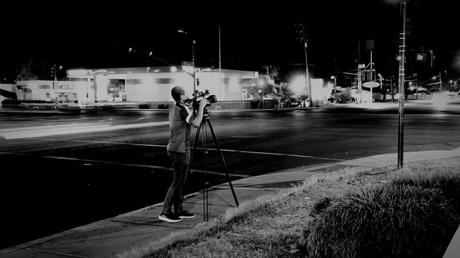 Man standing on illuminated street at night