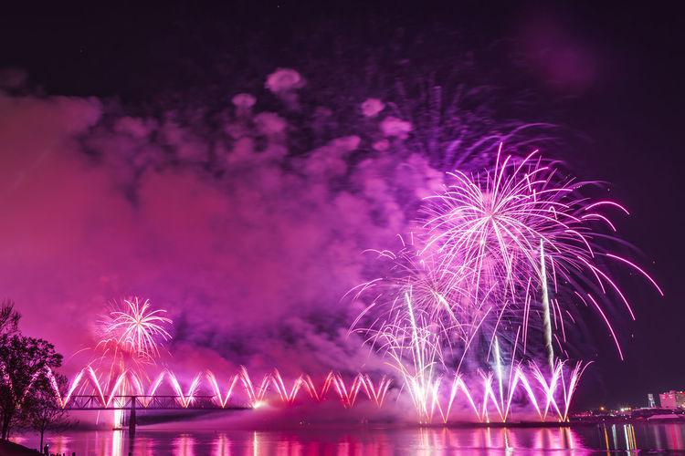 Illuminated firework display over river at night