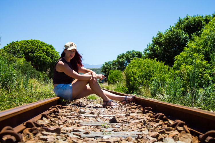Woman sitting on railroad track against clear sky