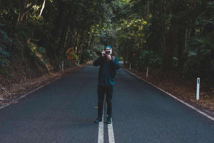 Man Photographing With Camera On Street Amidst Trees In Forest