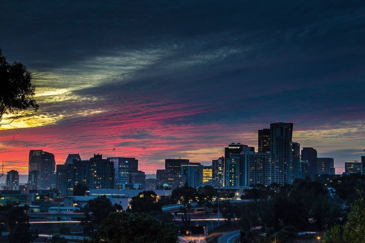 sunset, skyscraper, architecture, building exterior, sky, cloud - sky, cityscape, tree, no people, city, outdoors, built structure, travel destinations, illuminated, modern, urban skyline, nature, day