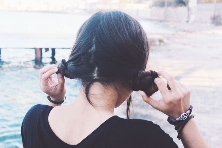 Rear view of woman holding pigtails