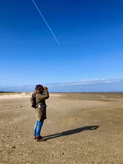 Full length of man standing against blue sky