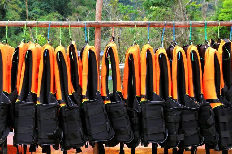 Hanging orange life jacket for safe life Float Swimming Accidents And Disasters Arrangement Black Boundary For Rent Hanging In A Row Jacket Large Group Of Objects Life Jacket Life Vest Lifeguard  Multi Colored Nature Orange Color Outdoors Protect Protection Safety Security Side By Side Sport
