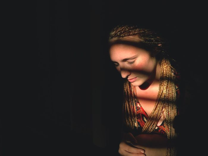 Close-Up Of Woman Standing Against Black Background