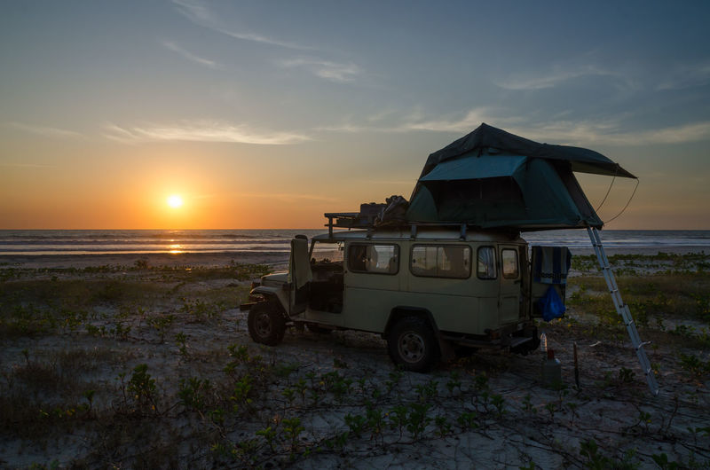Tent on vehicle at beach against sky during sunset