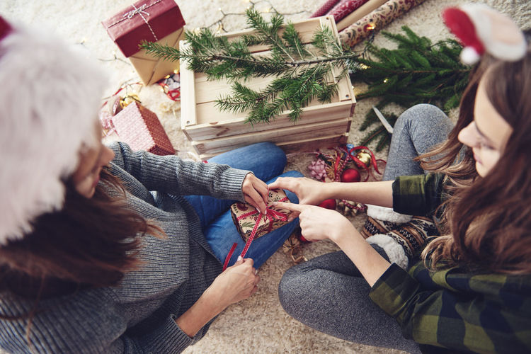 High angle view of friends decorating christmas presents at home